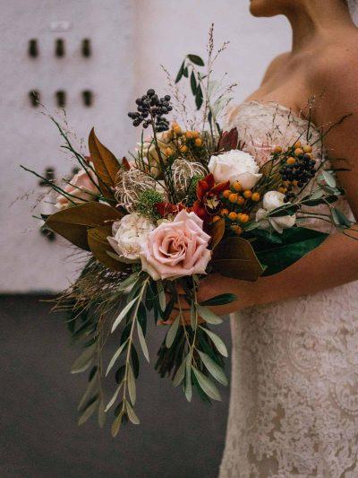 Nevesta se svatebni kytici v zimnich barvach s listy magnolie a olivovymi listy v interieru pivovaru Lobec