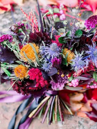 Podzimni svatebni kytice ladena do fialova a vinova s modrymi bodlaky