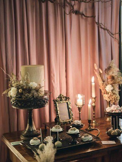 Svatebni sweet bar ozdobeny vintage dekoracemi, svickami a zivymi a susenymi kvetinami