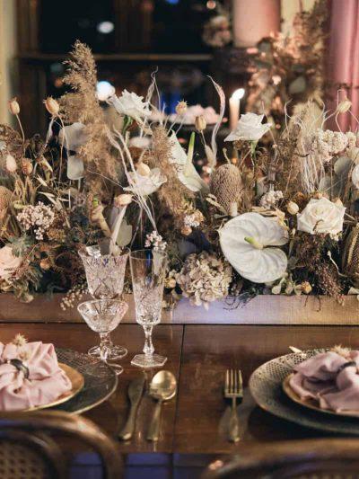 Svatebni dekorace z zivych a susenych kvetin na prostrene svatebni tabuli