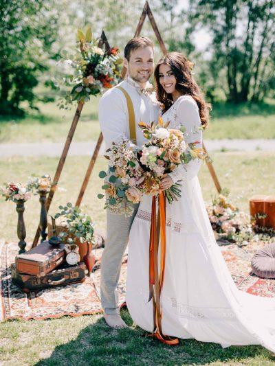 Nevesta a zenich s kvetinami a dekoracemi v boho stylu pred trojuhelnikovou svatebni branou pod sirym nebem