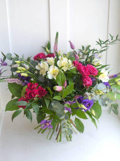 Bohata kytice cervenych, bilych a fialovych kvetu a rozmanite zelene.