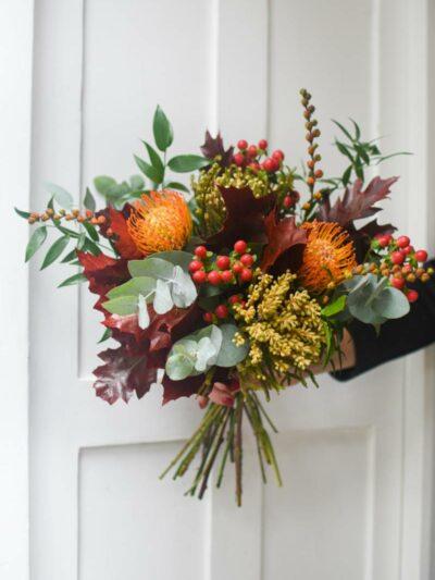 Leucosperm, hypericum and dark red oak leaves tied in a seasonal autumn bouquet