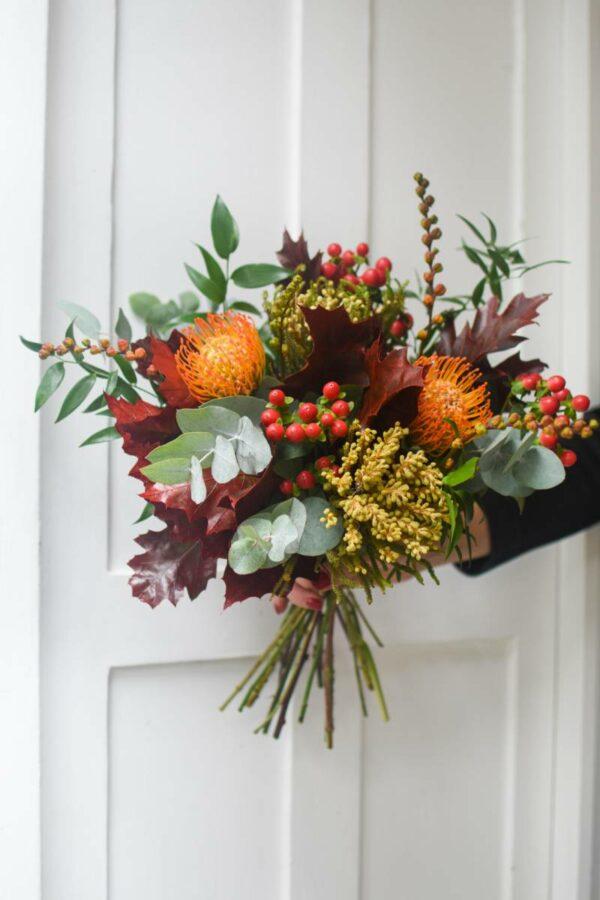 Leucospermem, hypericum a tmave cervene dubove listy uvazane v sezonni podzimni kytici